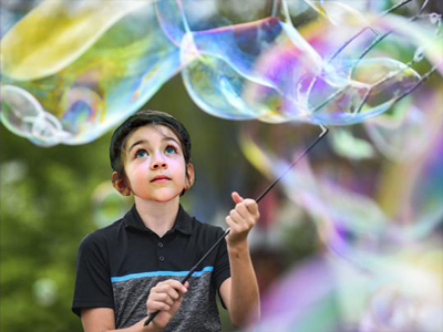 Picture of a young boy playing with a large bubble wand