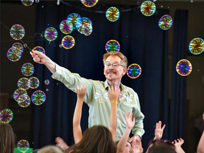 Picture of Steve Couch creating bubbles in front of an audience of children
